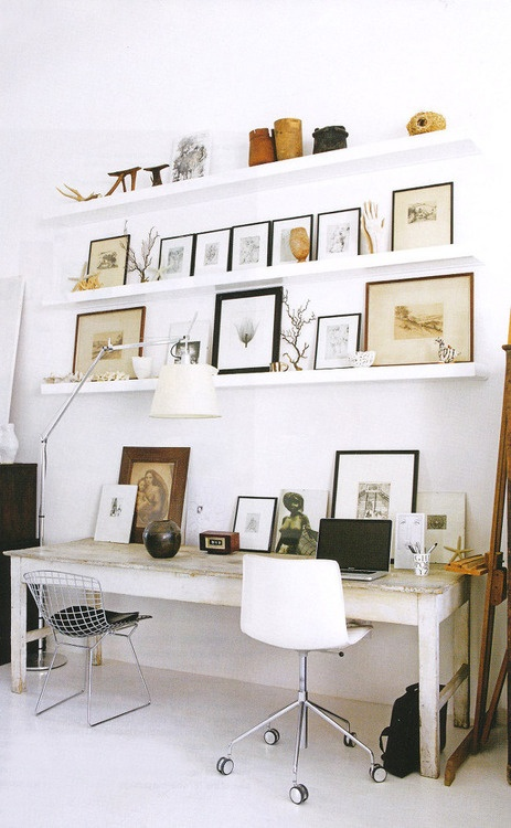 simple-white-home-office-designing-ideas-with-floating-shelves-and-full-of-picture-frames-above-small-wood-table-and-minimalist-chair